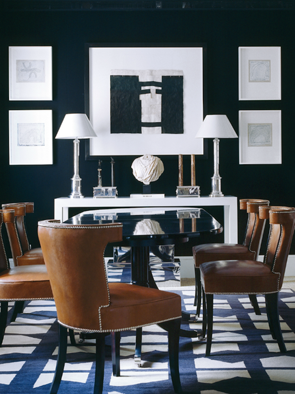 The patterned rug with the navy walls brings the drama to this dining room.