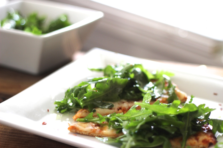 Dress up a pizza with arugula, grapeseed oil and a little balsamic drizzle