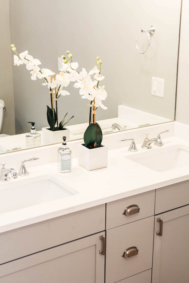 This is a peek in the master bathroom where we painted the vanity the same color as in the kitchen, switched the countertop for a white quartz (another classic choice) and added hardware, fixtures, lighting, etc. All the existing tile stayed and you can see more in this post.