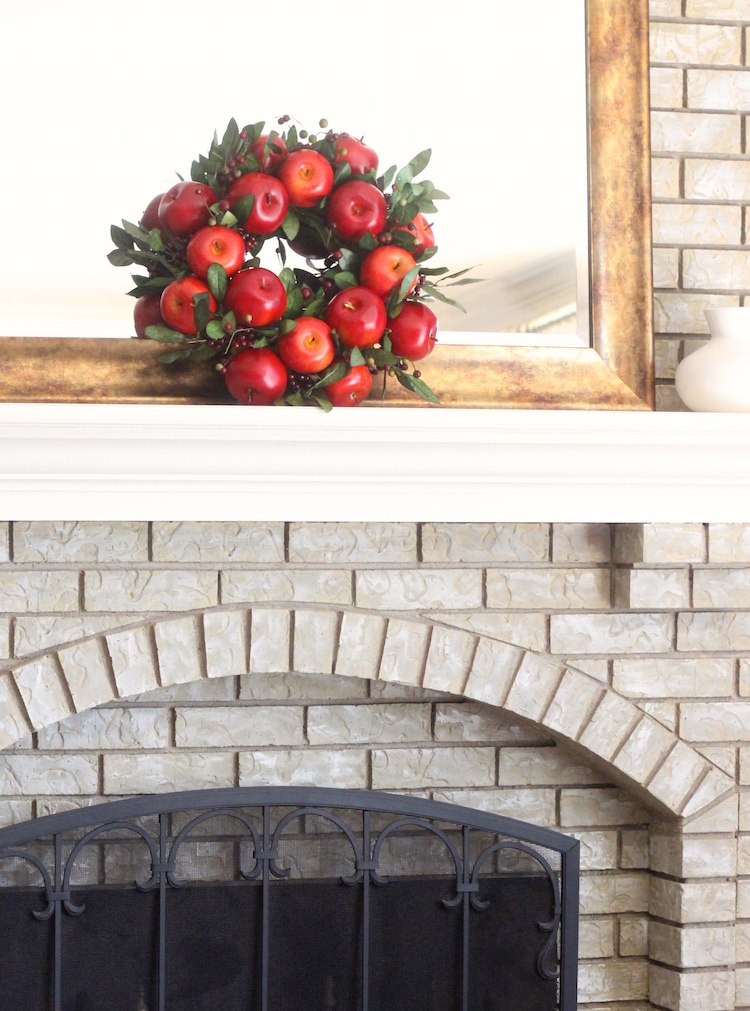 2. On the mantel Hang a wreath high, or have it sit on the mantel. This apple wreath comes in 2 sizes (small and large, link below) and this is the smaller size. It's sitting on a mantel in front of a mirror which is so simple but adds a lot. For more of a statement, go with the larger size (23 in diameter). I've seen wreaths in frames too on the mantel - so creative!